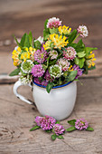 A bouquet of various types of clover in a jug