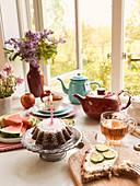 Teatime am geöffneten Fenster mit Brot, Kuchen und Obst