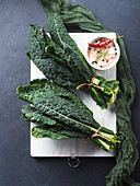 Raw black (Tuscan) kale on white chopping board with salt and spices.