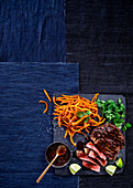 Beef rib-eye steak with ginger butter sauce and carrot fries