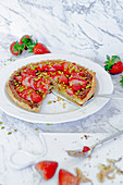 Puff pastry tart with strawberries and pistachios, a piece cut