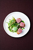 Saddle of lamb with tarragon honey, peas, and mountain cheese flan