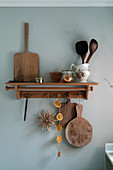 Kitchen utensils and chopping board on rustic shelf