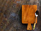 Holzbrett und Löffel auf braun-grauem Untergrund