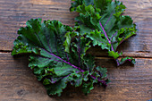 Two kale leaves on wooden background