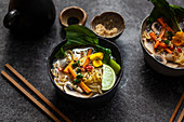 Noodle soup with carrots, mushrooms, pak choi and sesame seeds (Asia)