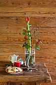 Amaryllis, Stechpalmenzweige und Lärchenweige in eine Glaswase