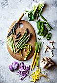 In Scheiben geschnittener grüner Spargel auf Holzbrett und frisches, buntes Gemüse
