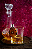 Glass of whiskey on wooden adn red background.