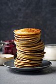 A stack of pancakes with jam and butter