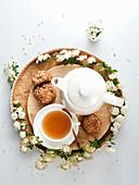 Teetasse, Teekanne, Plätzchen und weisse Blüten