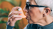 Senior woman using asthma inhaler with extension tube