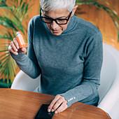 Senior woman using inhaler