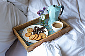 A breakfast tray with biscuits and coffee in bed