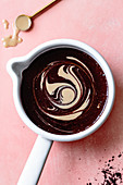 Swirls of salted tahini hot fudge sauce mixture in a saucepan