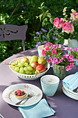 Fruit bowl and flower arrangement on table set for coffee