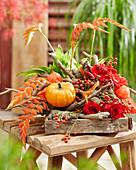 Herbstliches Gesteck mit Kürbis, Rosen, Gerbera, Hagebutten, Lampionfrüchten, Ästen und Bromelie