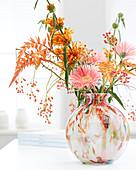 Herbststrauß in bunter Glasvase: Gerbera, Löwenohr, Bromelienblüten und Hagebutten