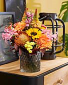 Herbststrauß aus Nadelkissen-Protea, Sonnenblume, Gerbera, Guernseylilie, Fackellilie, Hagebutten, Korallenbeeren und gefärbten Blättern