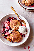 Cranberry apple cobbler with ice cream in a bowl.