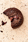 Closeup view of melted chocolate on a broken double chocolate ginger cookie.