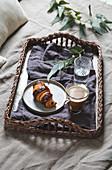 Frühstück im Bett mit Croissant und Kaffee auf Tablett