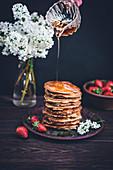 Ahornsirup fließt auf einen Stapel Pancakes