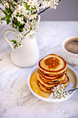 Stack of pancakes drizzled with maple syrup on a small white cake stand
