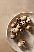 Quail eggs on a brown, speckled plate with a tan background.