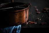 Melted dark chocolate in copper pot with drops going down side. Small metal whisk with chocolate, blue linen on a black wood surface. Dark, moody setting.