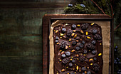 A tray of dark chocolate bark with fruit and nuts on a rustic wood board and distressed green table.