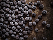 Frozen blueberries on a rustic metal surface.