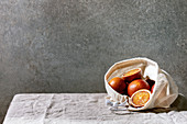 Blood sicilian oranges, ripe and juicy, in cotton eco friendly bag, whole and sliced, on grey linen table cloth, concrete wall as background.
