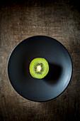 Kiwi Half on a black plate