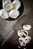 Button Mushrooms on a wooden board with a knife