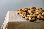 Traditional Swedish cardamom sweet buns Kanelbulle on cooling rack on beige linen table cloth.