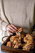 Woman in beige knitted sweater hold in hands wooden tray with home made traditional Swedish cardamom or cinnamon sweet buns Kanelbulle