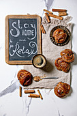 Traditional Swedish cinnamon sweet buns Kanelbulle on vintage tray, cup of coffee on linen cloth, chalkboard handwritten lettering Stay home and relax. White marble background, flat lay, space