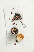 Dry rose buds tea in glass jar and tea strainer. Top view, flat lay