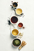 Cups of tea with aromatic dry tea in bowls on a white vintage background. Rose tea, green tea, black tea, rooibos tea, chamomile tea and matcha tea.