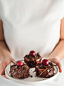 Woman in white t-shirt holds plate with three mini black forest cakes with cherry and chocolate shards. Vertical. Copy space top