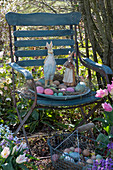 Osternest mit Osterhasen und Ostereiern auf Stuhl im Garten