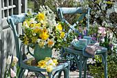Strauß aus Narzissen und Brautspiere auf Stühlen am Teehaus, Tablett mit Tassen