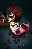 Pomegranate whole and in pieces with scattered seeds on a dark background.