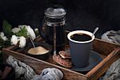 Schwarzer Kaffee serviert mit Schokoladenplätzchen auf Holztablett