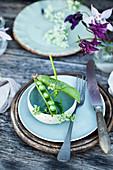 Ländliche Tischdeko mit Erbsenschote als Platzkarte, Wiesenkümmel und Akelei