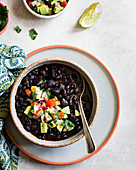 Black beans with avocado, tomato, red onion and cilantro in a bowl.