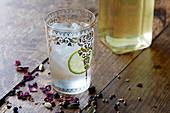 A glass of compound gin with ice cubes and a slice of lime