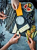 Halloween-Käseplatte mit schwarzen Grissini