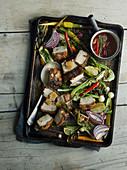 Schweinebauch mit Gemüse auf Ofenblech